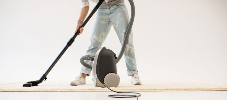 Man vacuuming the floors with a canister vacuum