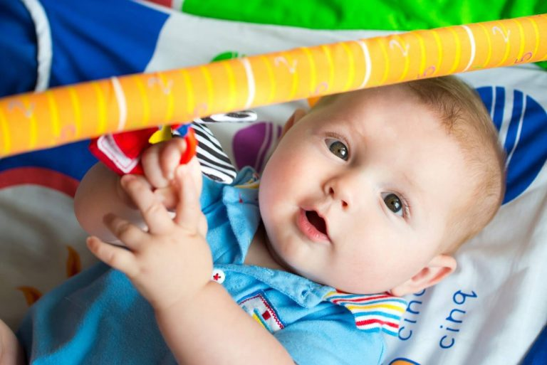 Baby in a blue shirt laying on a multi-colored play mat