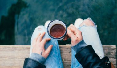 Man travelling to the lake and drinking a cup of coffee