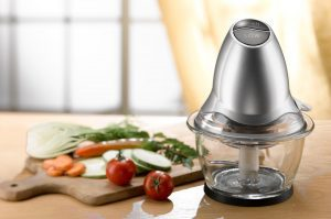 Mini food processor next to a wooden board of vegetables