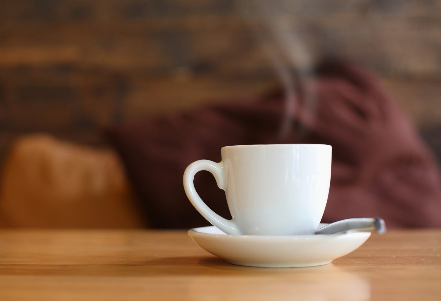 A hot cup of coffee served in a white cup