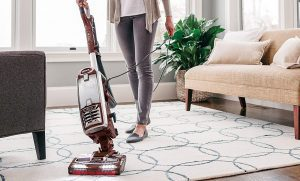 Woman cleaning floor with an upright vacuum