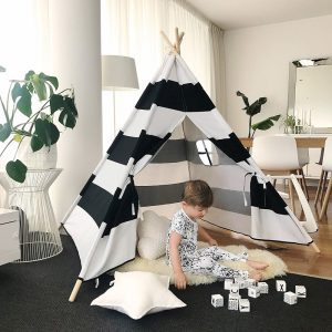Black and white teepee play tent on a black floor inside a living room