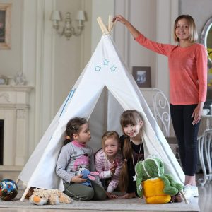 Three kids playing inside a wooden framed teepee tent with mom standing by the side