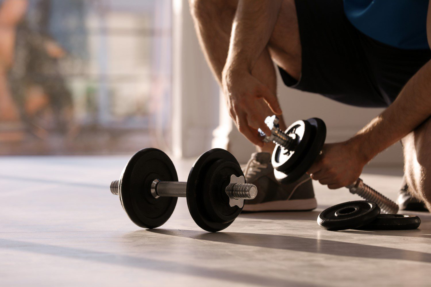 Man training his biceps in his living room with a pair of adjustable dumbbells