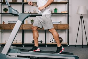 Man running on a compact treadmill in a small living room