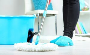 Person cleaning a white floor using a floor mop