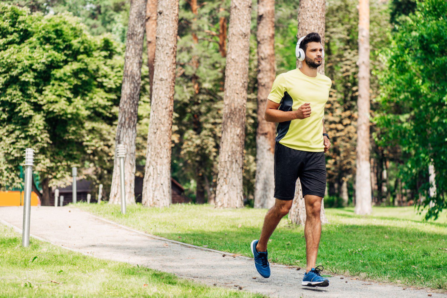 Man jogging through the woods while listening to music