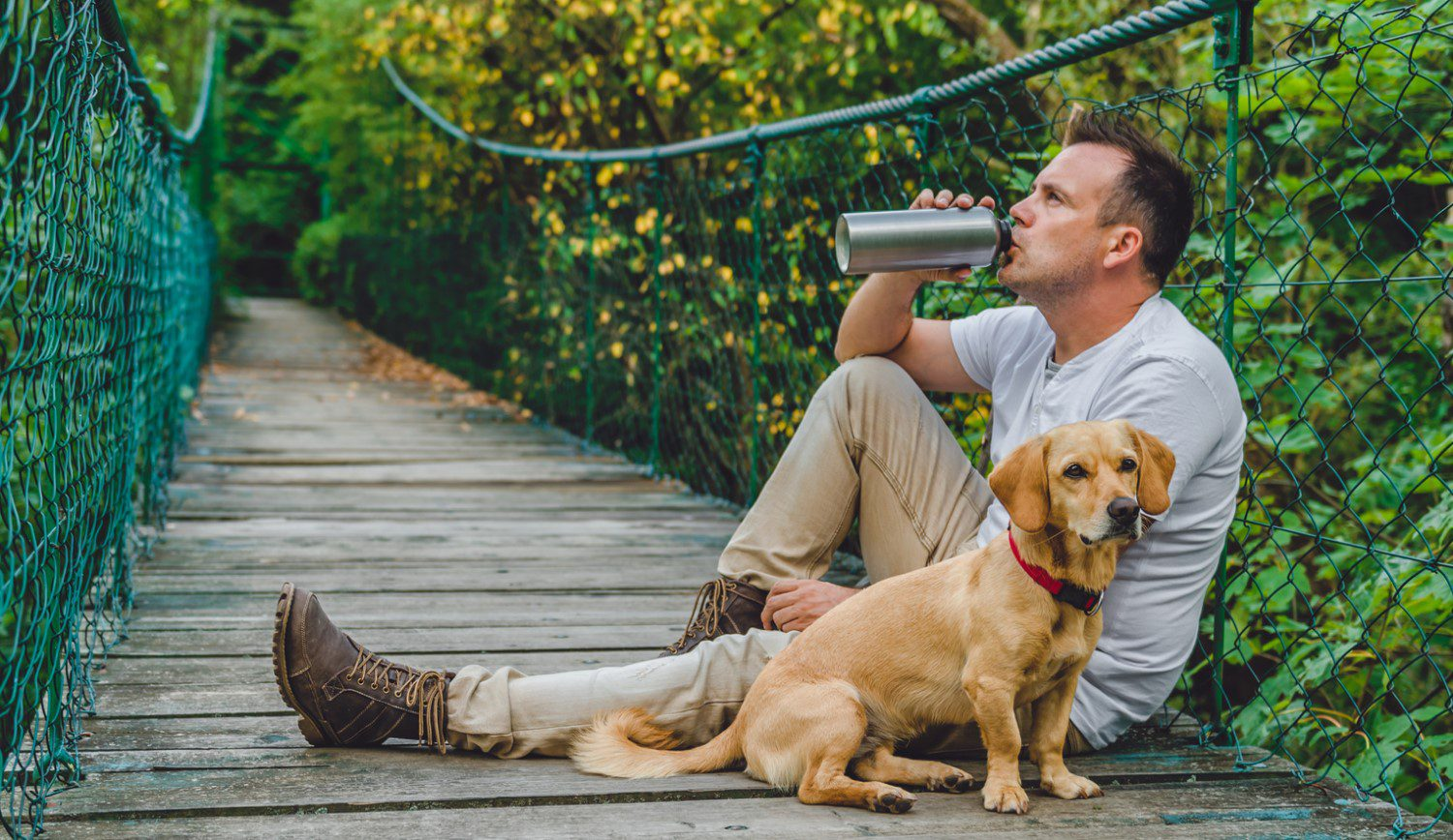 Male hiker taking a rest on a wooden bridge with his dog while drinking water