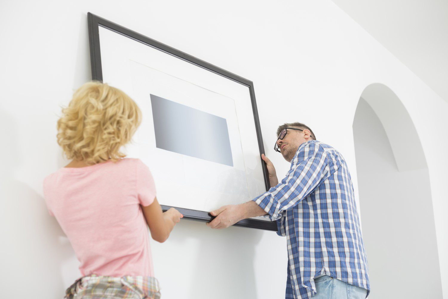 A couple attempting to hang a picture on a white wall