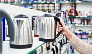 Customer reviewing electric kettles in a store
