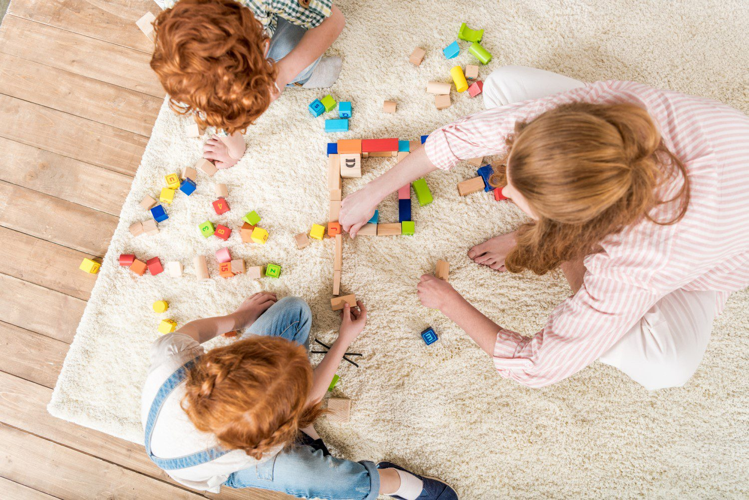 Three kids playing with toys on an area rug