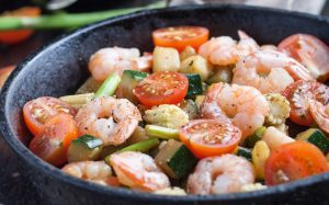 Shrimps and vegetables cooked in a cast iron wok