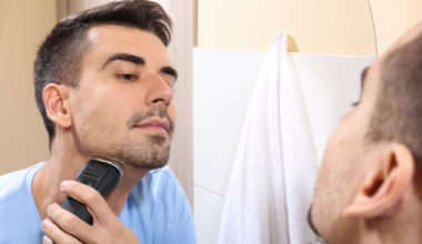Man looking at himself in mirror while shaving his facial hair with an electric razor