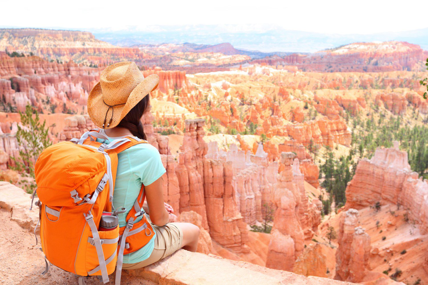 Female hiker taking a rest at the canyons with her orange backpack