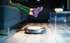 Robot vacuum cleaning the floor quietly while owner sits in sofa