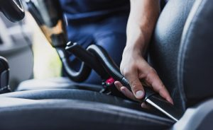Man cleaning a car seat with a handheld vacuum cleaner