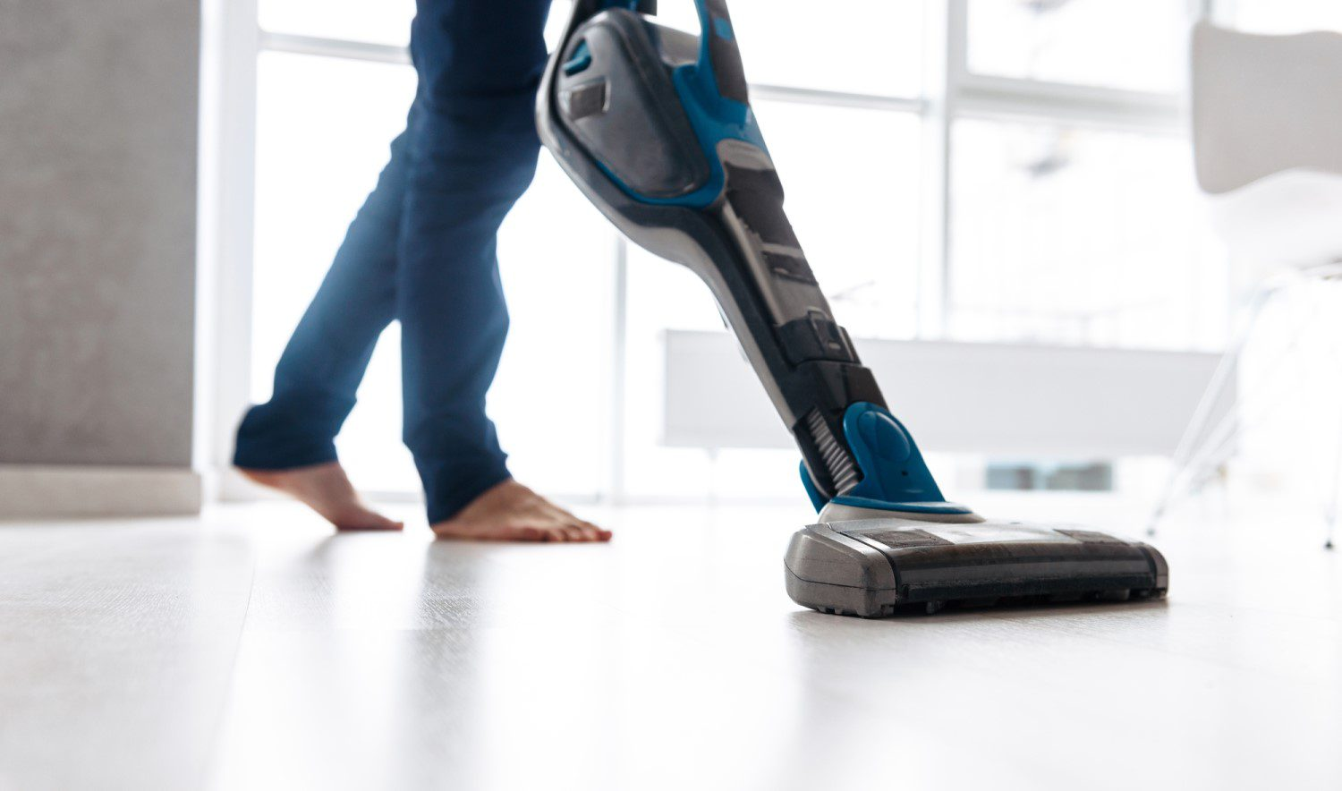 Person using a stick vacuum on a floor
