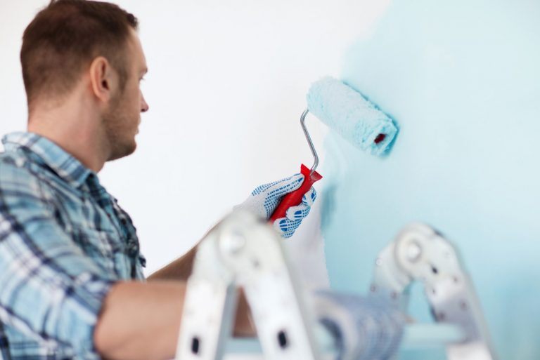 Male painter in the process of painting a blue wall