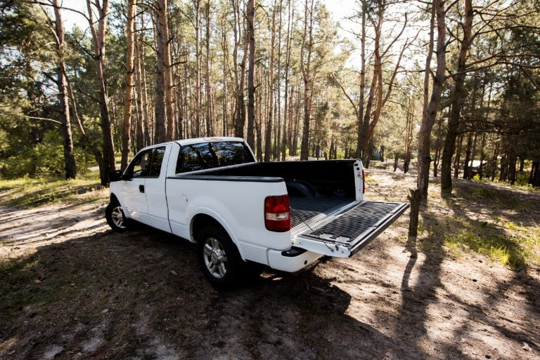 White truck in a forest with the flatbed open