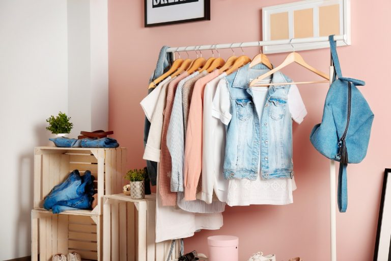 Clothes stored on a rack without a dresser