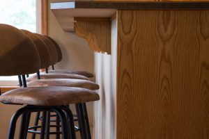 Bar stools with back placed in a row near a bar table