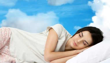 Woman sleeping with blue sky in the background