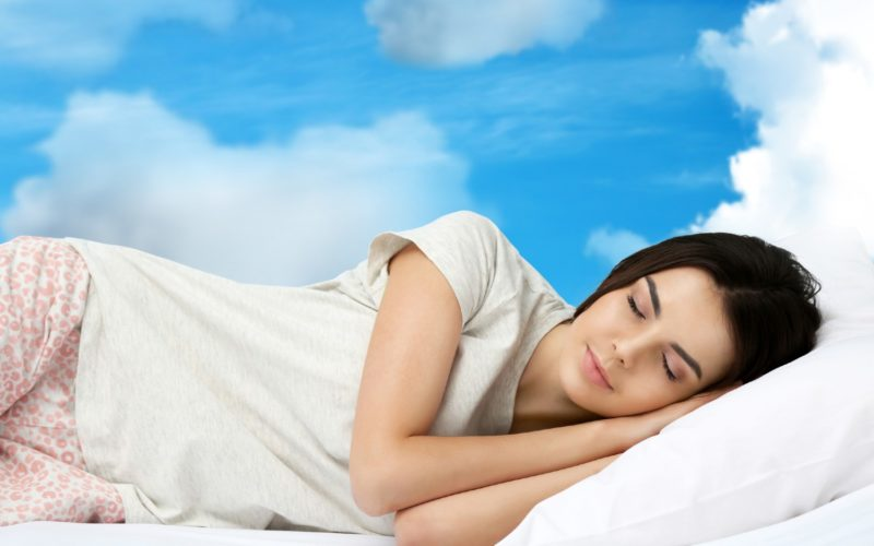 A picture of a woman sleeping with blue sky in the background