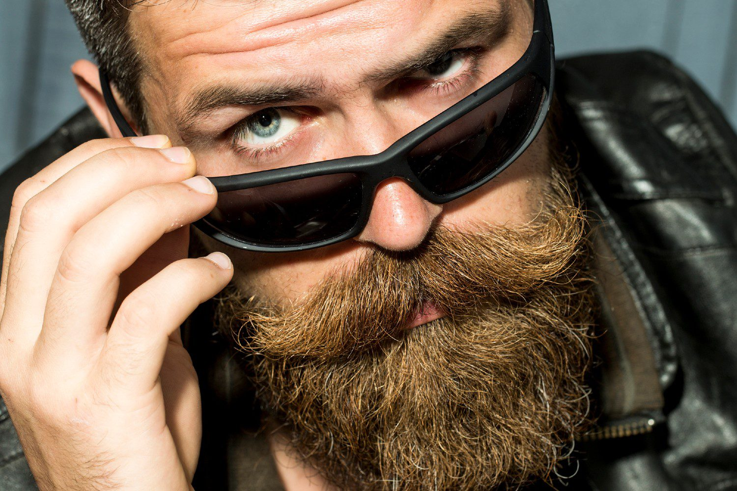 Man with sunglasses and a very thick beard looking into the camera