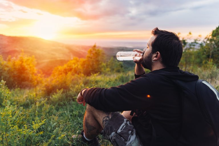 Man taking a break with a collapsible water bottle during his hike