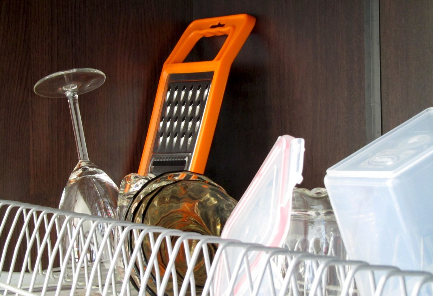 Dishes and cutlery drying on a rack on top of a shelf