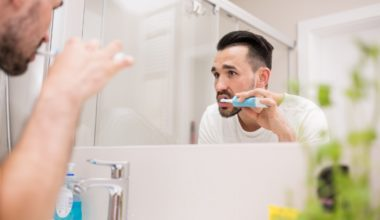 Man brushing his teeth in front of the mirror using an electric tooth brush