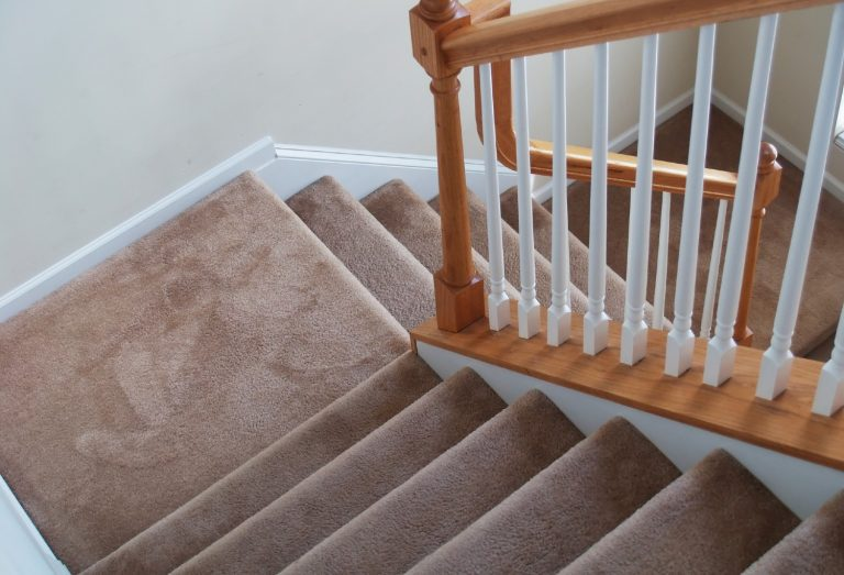 Stairs with a brown carpet and white-brown wooden railing