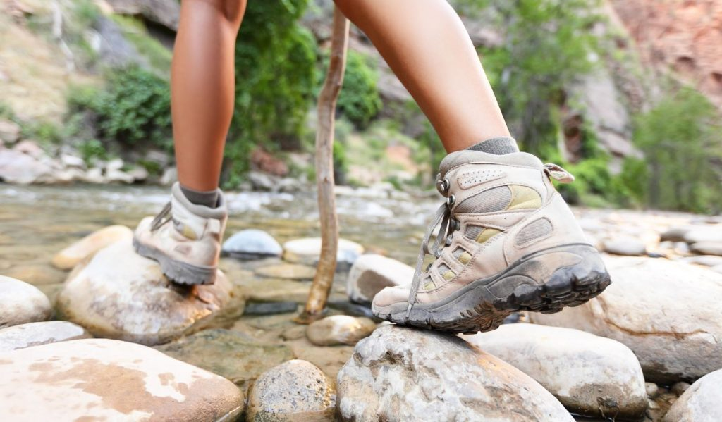 Woman wearing hiking boots while walking on stones