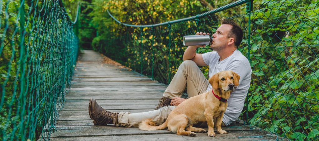 Male taking a break during a hike with his dog