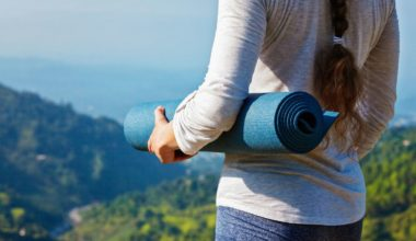 Woman standing on a mountain with her yoga mat in hand