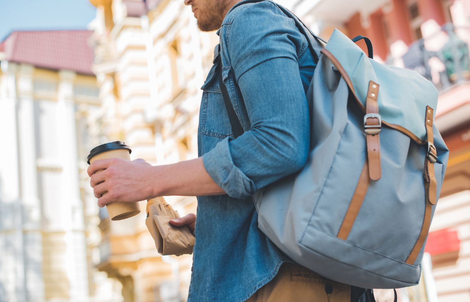 Man commuting through the city with his backpack and a cup of coffee