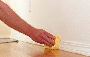 Wiping the baseboards to get them clean