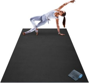 Woman doing yoga exercise on a large yoga mat