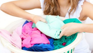 Woman folding laundry from a laundry hamper