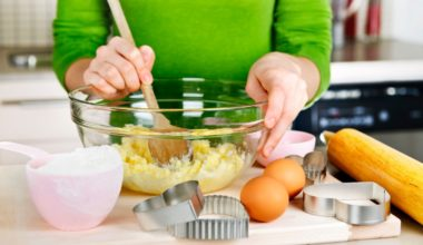 Woman mixing ingredient in a glass bowl in a kitchen