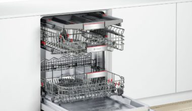 Large dishwasher with the door opened and baskets slided out