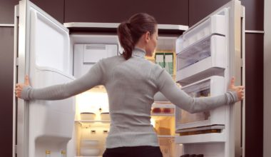 Woman standing in front of an open French door refrigerator