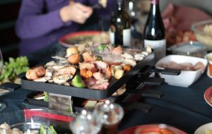 Group of people sitting around a table while cooking their food on a raclette grill