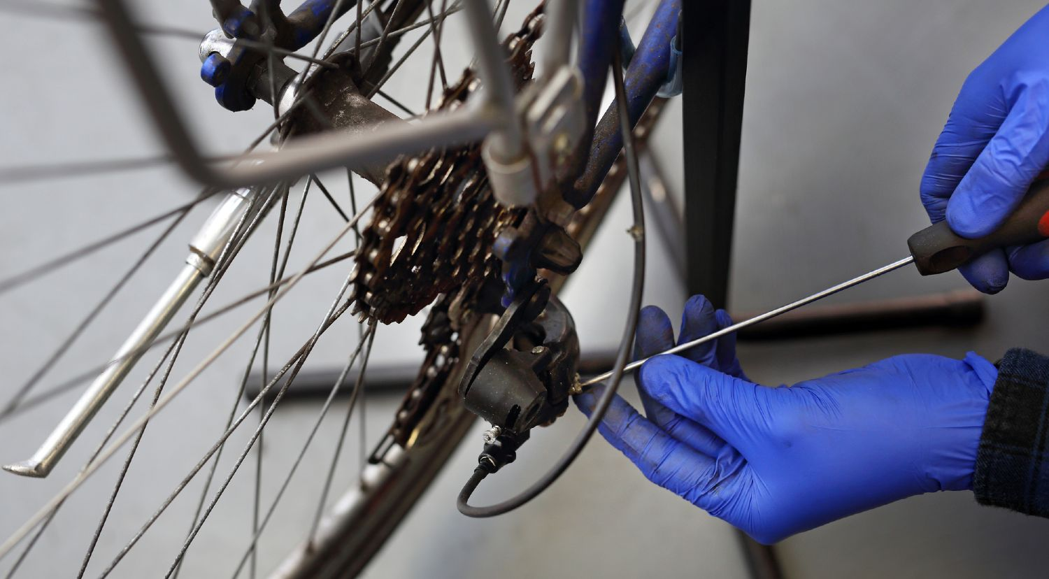 Bicycle getting repaired by a person wearing blue gloves