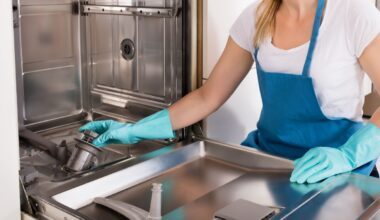 Woman in gloves cleaning an empty dishwasher