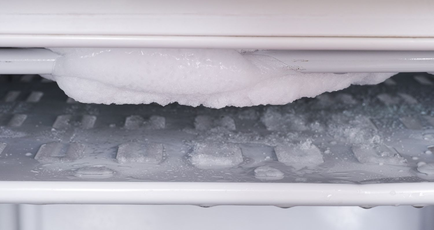 View of an open freezer with ice hanging from the ceiling