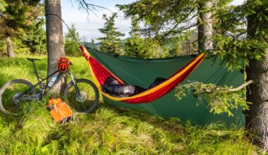 Camping in an orange hammock under a green tarp in a forest