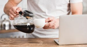 Man in white t-shirt standing behind a wooden countertop while pouring a cup of coffee