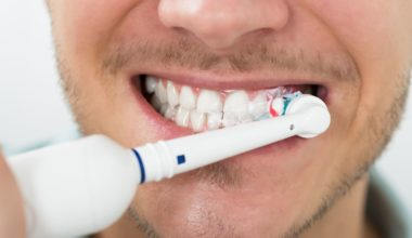 Man brushing teeth with his mouth wide open using an electric toothbrush